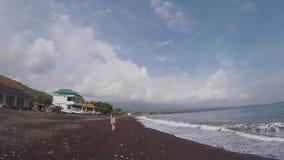Een meisje in de afstand loopt blootvoets op een mooi zwart strand van vulkanisch zand stock videobeelden