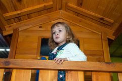 Een meisje in de spelen van de denimoverall in een houten spelhuis op de speelplaats in het gokkencentrum Stock Afbeelding