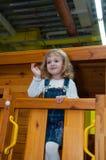 Een meisje in de spelen van de denimoverall in een houten spelhuis op de speelplaats in het gokkencentrum Royalty-vrije Stock Afbeeldingen