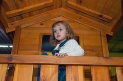 Een meisje in de spelen van de denimoverall in een houten spelhuis op de speelplaats in het gokkencentrum Stock Foto