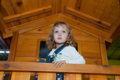 Een meisje in de spelen van de denimoverall in een houten spelhuis op de speelplaats in het gokkencentrum Royalty-vrije Stock Fotografie