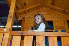Een meisje in de spelen van de denimoverall in een houten spelhuis op de speelplaats in het gokkencentrum Stock Fotografie