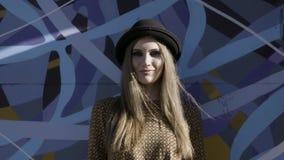 Een meisje in de stadsstraat die zwarte hoed dragen en het moeras kleuren overhemd op blauwe graffityachtergrond actie Mooie vrou stock video