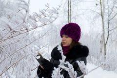 Een meisje in de winter kleedt Foto's van struiken met mooie rijp worden behandeld die stock afbeelding