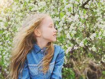 Een meisje in een denimoverhemd in de wind in een kersenboomgaard Stock Fotografie