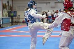 Een meisje die aan Taekwondocompetities deelnemen in een blauw beschermend vest en een beschermende helm is een duel in Taekwondo stock fotografie