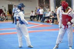 Een meisje die aan Taekwondocompetities deelnemen in een blauw beschermend vest en een beschermende helm is een duel in Taekwondo stock afbeeldingen