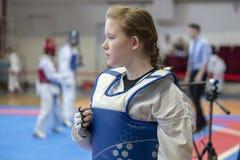 Een meisje die aan Taekwondocompetities deelnemen in een blauw beschermend vest op de achtergrond van Taekwondocompetities stock afbeelding