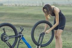 Een meisje die een bergfiets op een asfaltweg, mooi portret berijden van een fietser stock foto