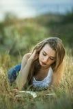 Een meisje die een boek buiten lezen Stock Afbeeldingen