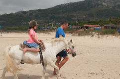 Een meisje die een paard met een trainer berijden Stock Afbeeldingen