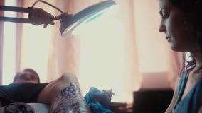 Een meisje die een tatoegeringsmachine houden die en in een patroon op de huid toepast stock videobeelden