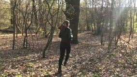 Een meisje die en in een bos achter bomen lopen verbergen stock videobeelden