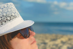 Een meisje die glazen en een witte hoed dragen ligt bij nacht op het strand tegen de achtergrond van zand en hemel Het portret stock foto's