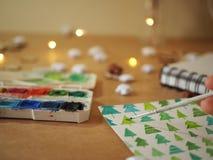 Een meisje die groene Kerstbomen op een wit blad van document met verven schilderen stock afbeeldingen