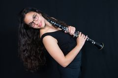 Een meisje die haar instrument van de klarinetmuziek houden Cijfer tegen een zwarte achtergrond royalty-vrije stock afbeeldingen