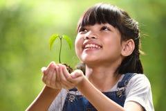 Een meisje die een jonge plant in haar handen met een hoop van goed milieu houden stock foto