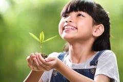 Een meisje die een jonge plant in haar handen met een hoop van goed milieu, selectieve nadruk op installatie houden stock foto's