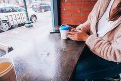 Een meisje die een kop van koffie met een blauw deksel houden stock foto's