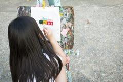 Een meisje die op canvas schilderen Stock Foto