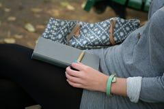 Een meisje die op de bank met haar blocnote en potlood situeren die op de ideeën wachten te schrijven Royalty-vrije Stock Foto's