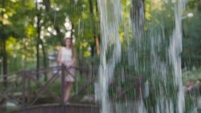 Een meisje die in een park op een brug lopen die het gietende water van een fontein bekijken stock footage