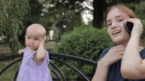 Een meisje die rond terwijl het spreken op de telefoon kijken Een babymeisje in purple bevlekte kleding houdt haar hand door het  stock video