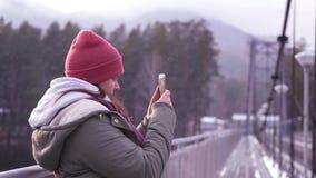 Een meisje die zich op een brug in een jasje bevinden maakt een panorama van het landschap op haar telefoon langzame motie, 1920x stock video