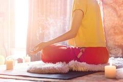 Een meisje door kaarsen thuis bij het venster wordt omringd mediteert in de lotusbloempositie die vingersmudra die naast maken royalty-vrije stock foto