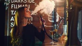 Een meisje drinkt een cocktail en rookt de waterpijp bij de barteller in 4k resolutie in langzame motie stock video