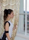 Een meisje in een baltoga die zich door het venster bevindt Royalty-vrije Stock Afbeelding