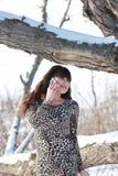 Een meisje in een kleding dichtbij de oude eiken boom op de telefoon royalty-vrije stock foto's