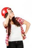 Een meisje in een rode helm bekijkt omhoog witte achtergrond in een overhemd in een cel Royalty-vrije Stock Afbeelding
