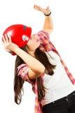Een meisje in een rode helm met ontzetting kijkt omhoog Stock Foto's