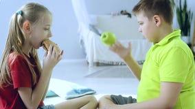 Een meisje eet een Hamburger en een jongen speelt met Apple stock footage