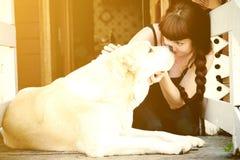 Een meisje en een grote witte hond die in elkaar staren de ogen van ` s, omhelzen en kussen Royalty-vrije Stock Afbeeldingen