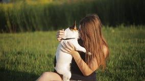 Een meisje en een hond kussen in aard zij een hond draagt stock video
