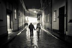 Een meisje en een jongen die in de oude stadsstraat bij nacht lopen, haldin Royalty-vrije Stock Afbeeldingen