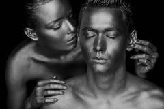 Een meisje en een kerel in gouden verf wordt behandeld die Met mijn gesloten ogen Het geleunde meisje, Zwart-wit Stock Foto