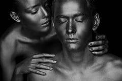 Een meisje en een kerel in gouden verf wordt behandeld die Met mijn gesloten ogen Het geleunde meisje, Zwart-wit Royalty-vrije Stock Afbeelding