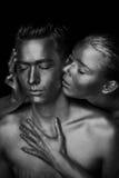 Een meisje en een kerel in gouden verf wordt behandeld die Met mijn gesloten ogen Het geleunde meisje, Zwart-wit Royalty-vrije Stock Fotografie