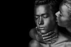 Een meisje en een kerel in gouden verf wordt behandeld die Met mijn gesloten ogen Het geleunde meisje, Zwart-wit Royalty-vrije Stock Foto