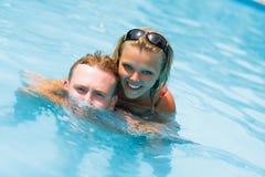 Een meisje en een mens zijn in blauw water stock foto's