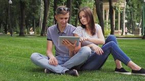 Een Meisje en Guy Use een Digitale Tablet stock video