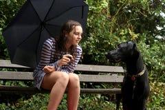 Een meisje en haar hond het spelen in de regen stock afbeelding
