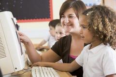 Een meisje en haar leraar die aan een computer werken Royalty-vrije Stock Afbeelding