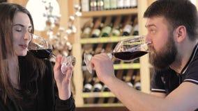 Een meisje en een kerel in een restaurant delen en drinken rode wijn, een jonge rode wijn van paardranken bij een lijst in a mee stock video