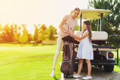 Een meisje en een vrouw krijgen de golfclubs uit de zak Stock Foto's