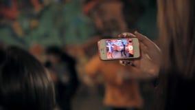 Een meisje filmt een onderbrekingsdans op haar smartphone stock videobeelden
