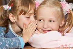 Een meisje fluistert in het oor van haar meisje royalty-vrije stock foto
